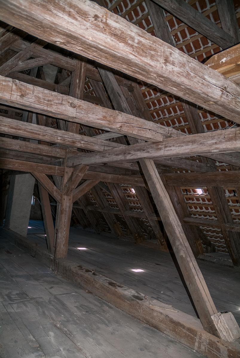 I loftsrummet, der er 44 m langt og 11 m bredt, kan man se den mægtige konstruktion af svære bjælker, der er tappet sammen.